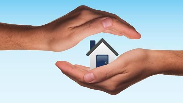 Themenbild: Schützende Hände um ein Eigenheim