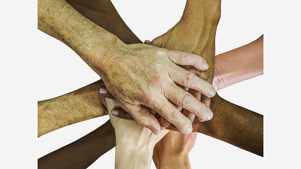 Themenbild: übereinandergelegte Hände als Zeichen der Verbundenheit