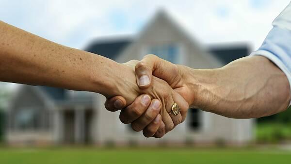 Themenbild: Vordergrund: Handschlag, Hintergrund: Haus mit Garten
