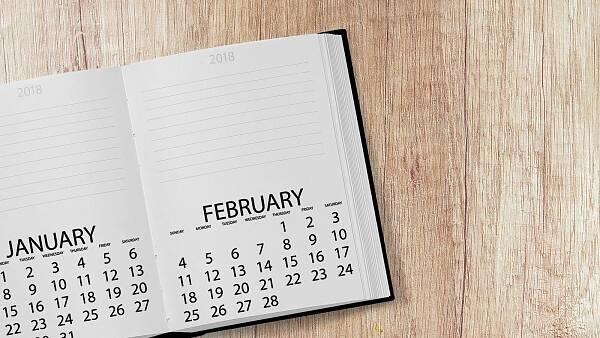 Themenbild: aufgeschlagener Kalender auf einem Holztisch