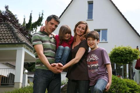 Familie vor Haus im Garten