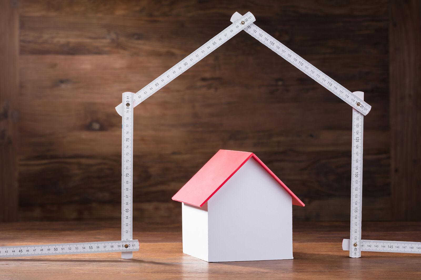 Ein Modell-Häuschen mit rotem Dach unter einem Zollstock