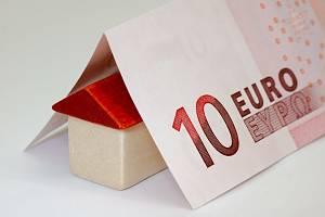 Ein kleines Spielzeughaus unter einem Zehn-Euro-Schein
