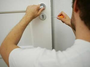 Ein Handwerker öffnet eine Haustür.