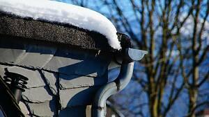Dachrinne und Fallrohr an einem mit Schnee bedeckten Dach