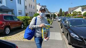 ein junger Mann mit Maske trägt einen Einkaufsbeutel