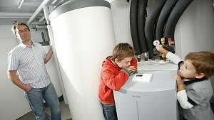 Vater mit zwei Jungs schaut sich die Wärmepumpe im Keller an.