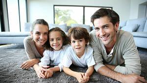 Familie auf Teppich im Wohnzimmer