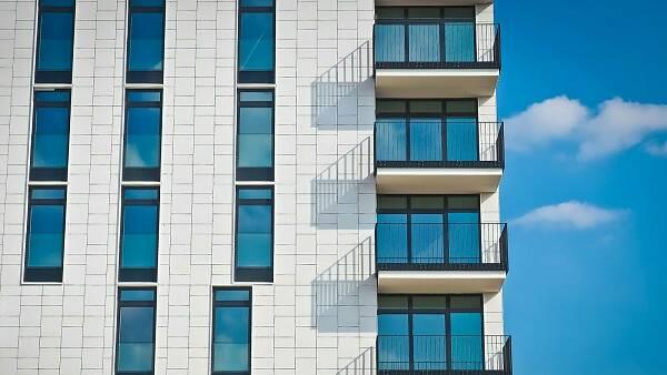 Themenbild: Mehrfamilienhaus mit Balkonen vor blauem Himmel