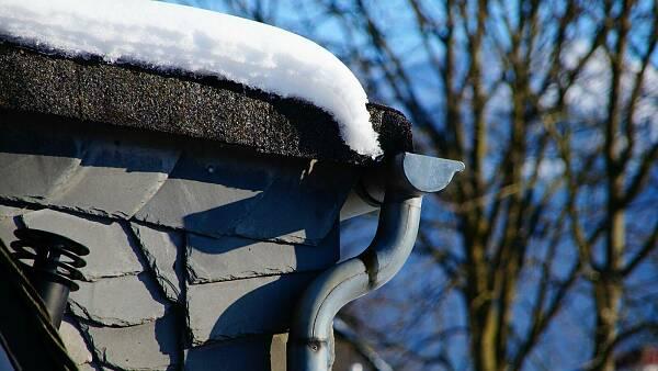 Themenbild: Dachrinne und Fallrohr an einem mit Schnee bedeckten Dach
