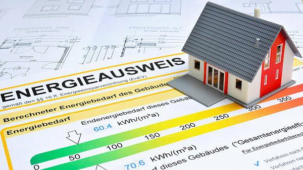 Themenbild: Kleines Modell eines Hauses steht auf einem Energieausweis.