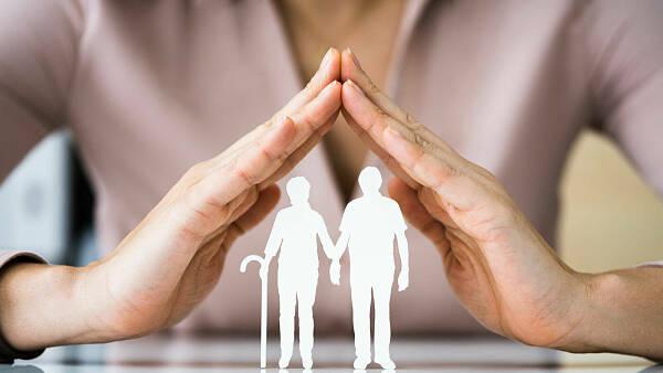 Themenbild: zwei Hände werden schützend über ein Scherenschnitt-Paar gehalten