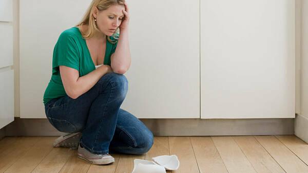 Themenbild: Frau vor zerbrochenem Porzellan