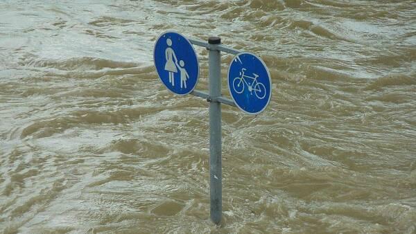 Themenbild: Ein Straßenschild im Hochwasser