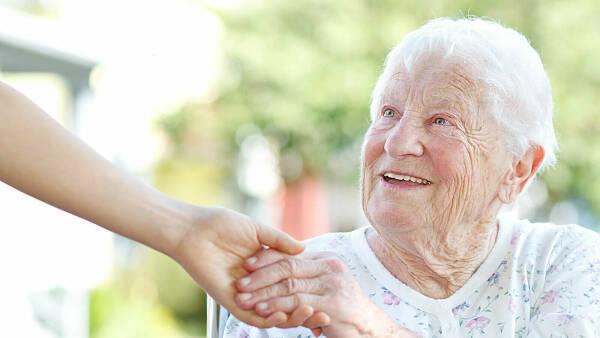 Themenbild: Eine weißhaarige alte Dame hält die Hand eines Betreuers.