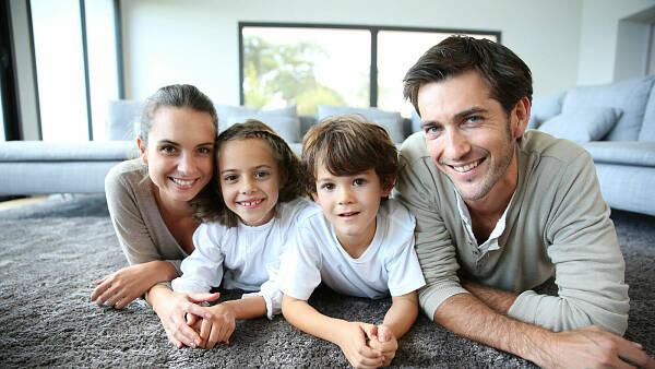Themenbild: Familie auf Teppich im Wohnzimmer
