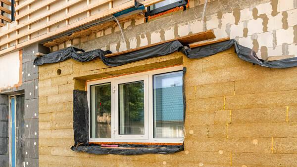 Themenbild: Ansicht eines Hauses, dass gedämmt wird