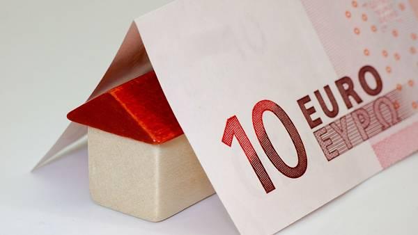 Themenbild: Ein kleines Spielzeughaus unter einem Zehn-Euro-Schein