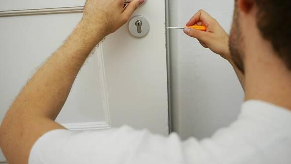 Themenbild: Ein Handwerker öffnet eine Haustür.