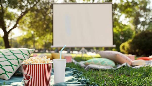 Themenbild: Popcorn und Kissen im Garten vor einer großen Leinwand
