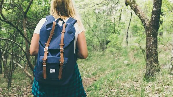 Themenbild: Wanderin mit Rucksack auf Weg