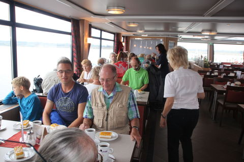 Die Teilnehmer lassen sich Kaffee und Kuchen auf dem Schiff schmecken.